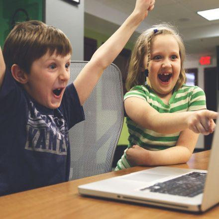 Boy and girl at computer cheering