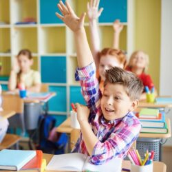 Happy Kids Raising Their Hands While Sitting At School Desks