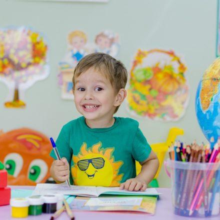 Smiling boy coloring