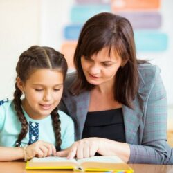 Female Teacher And Student Reading Book Together At Table