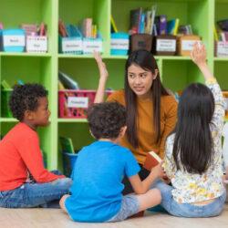 Enthused Kids Sitting In Half Circle Around Teacher Copy
