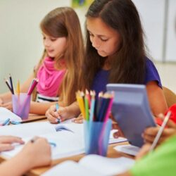 Two Female Students Coloring At Table While Smiling