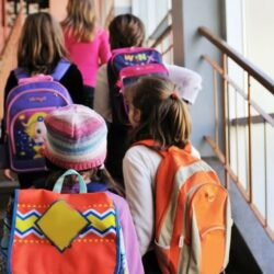 Group Of Girl Students Walking Up Stairs With Colorful Backpacks
