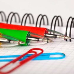 Colorful Pens Lying On Notebook With Paper Clips