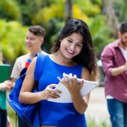 Female Mexican Student Smiling While Holding Notebook