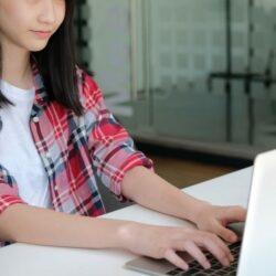 Girl In Plaid Shirt Typing On Laptop