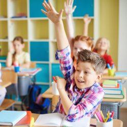 Happy Kids Raising Their Hands While Sitting At School Desks