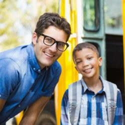 Teacher And Young Male Student Smiling At The Door Of A School Bus