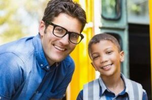 Young Male Student Smiling At The Door Of A School Bus